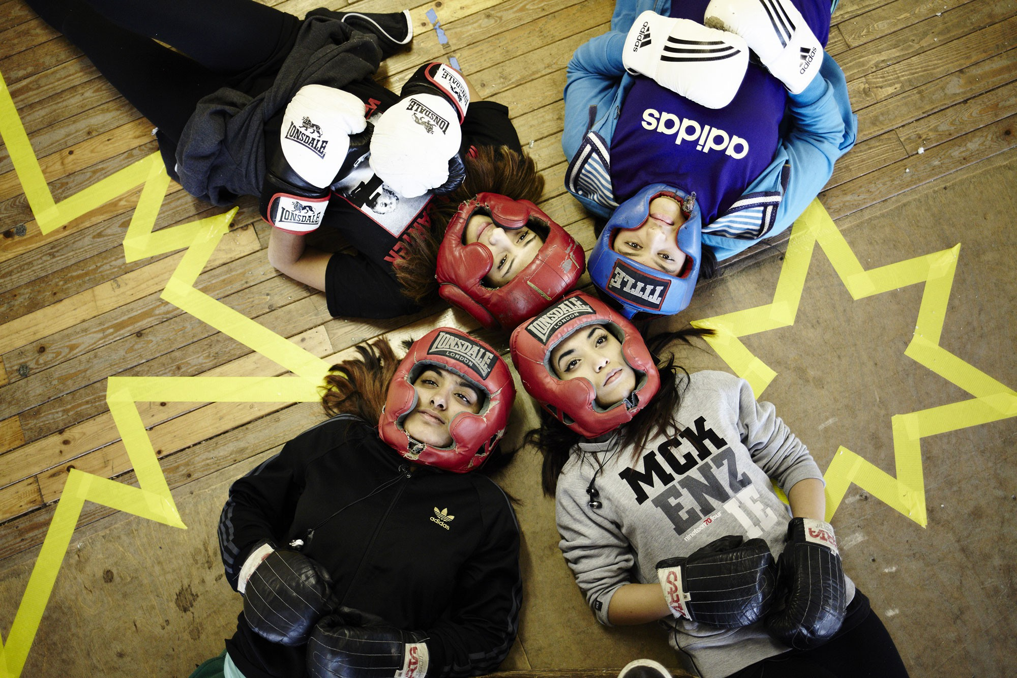 Performers from the site-specific theatre piece No Guts No Heart No Glory, about female muslim boxers, in boxing gear lying on the floor.