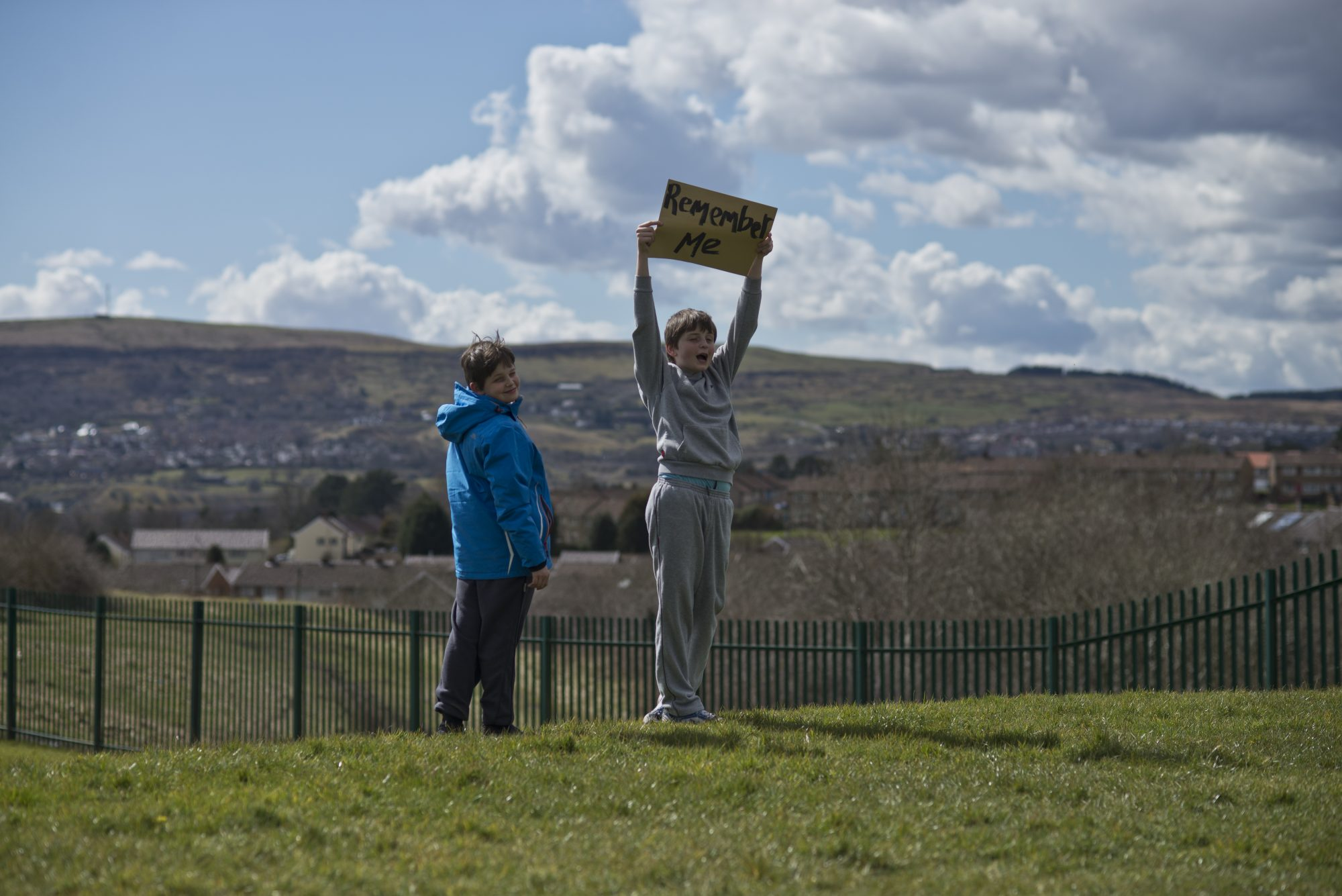 Two people stand on a hill, one holds a sign above his head