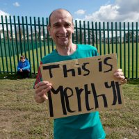 A man holds a handwritten sign that says 'This is Merthyr'