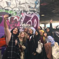 A selfie of the Speakers Corner girls at the southbank centre underground skatepark, in front of some graffiti.