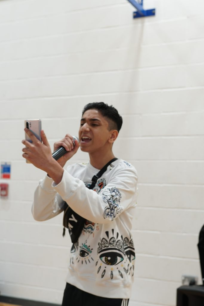 A teenage boy performs into a mic whilst looking at his phone