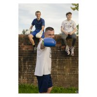 Photograph of 3 male boxers. 2 sit on a wall. One in the forground rasies a punch towards the camera