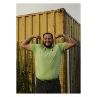 A man stands in front of a yellow shipping container. He is wearing a lime green t-short and is flexing his arm muscles and smiling.