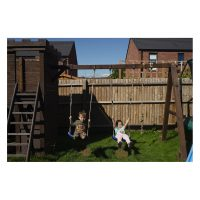 Two kids swing on swings in a garden