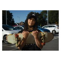 A young woman wearing a baseball hat hugs her skateboard