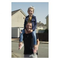 A man has his daughter sitting on his shoulders in the street