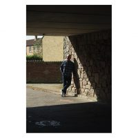 A man leans in the wall in an underpass. He is standing in the sunshine.