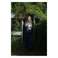 A woman with dreadlocks stands in the doorway of an overgrown greenhouse