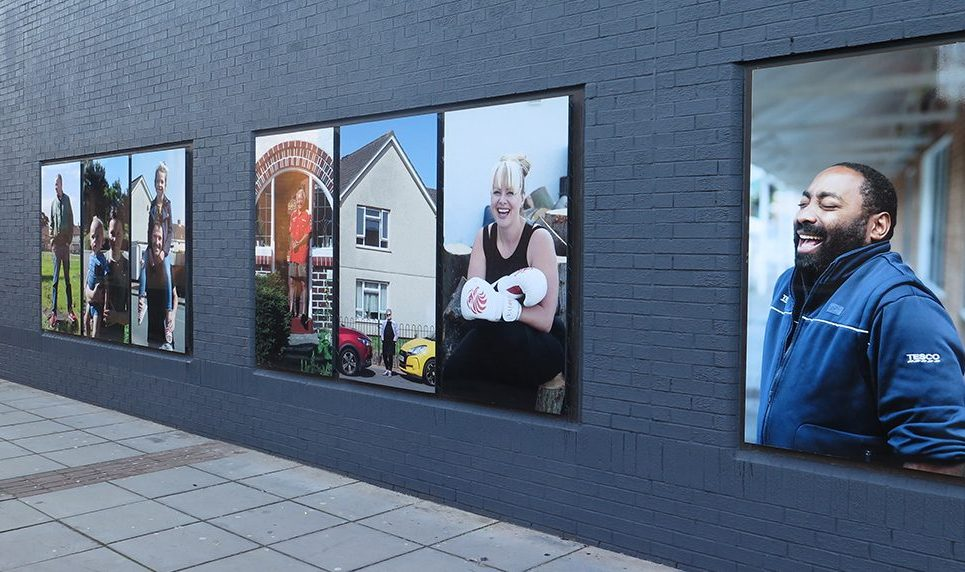 an installation of larger than life photographic portraits outdoors, on a grey wall.