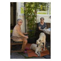 Two women sit in a garden with two dogs
