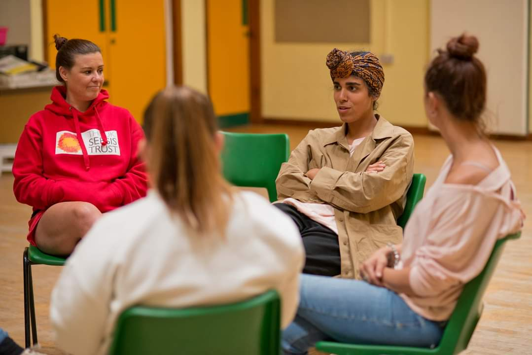 4 women in conversation, sit on chairs in a circle