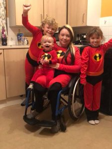 Rhian and her three children are dressed as 'The Incredibles'. Rhian is sitting in a wheelchair, holding her youngest child on her lap.