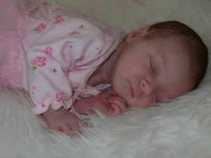 A baby asleep on a sheepskin