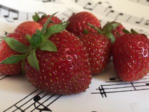 A close up of strawberries, on musical notation