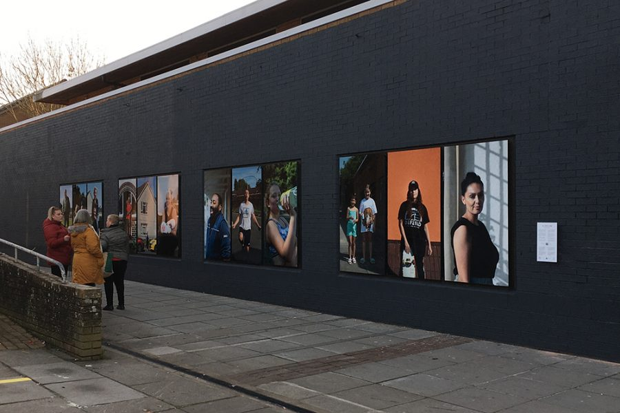 An outdoor exhibition of large portraits of people, installed on a grey wall. A group of women stand looking at the photos.