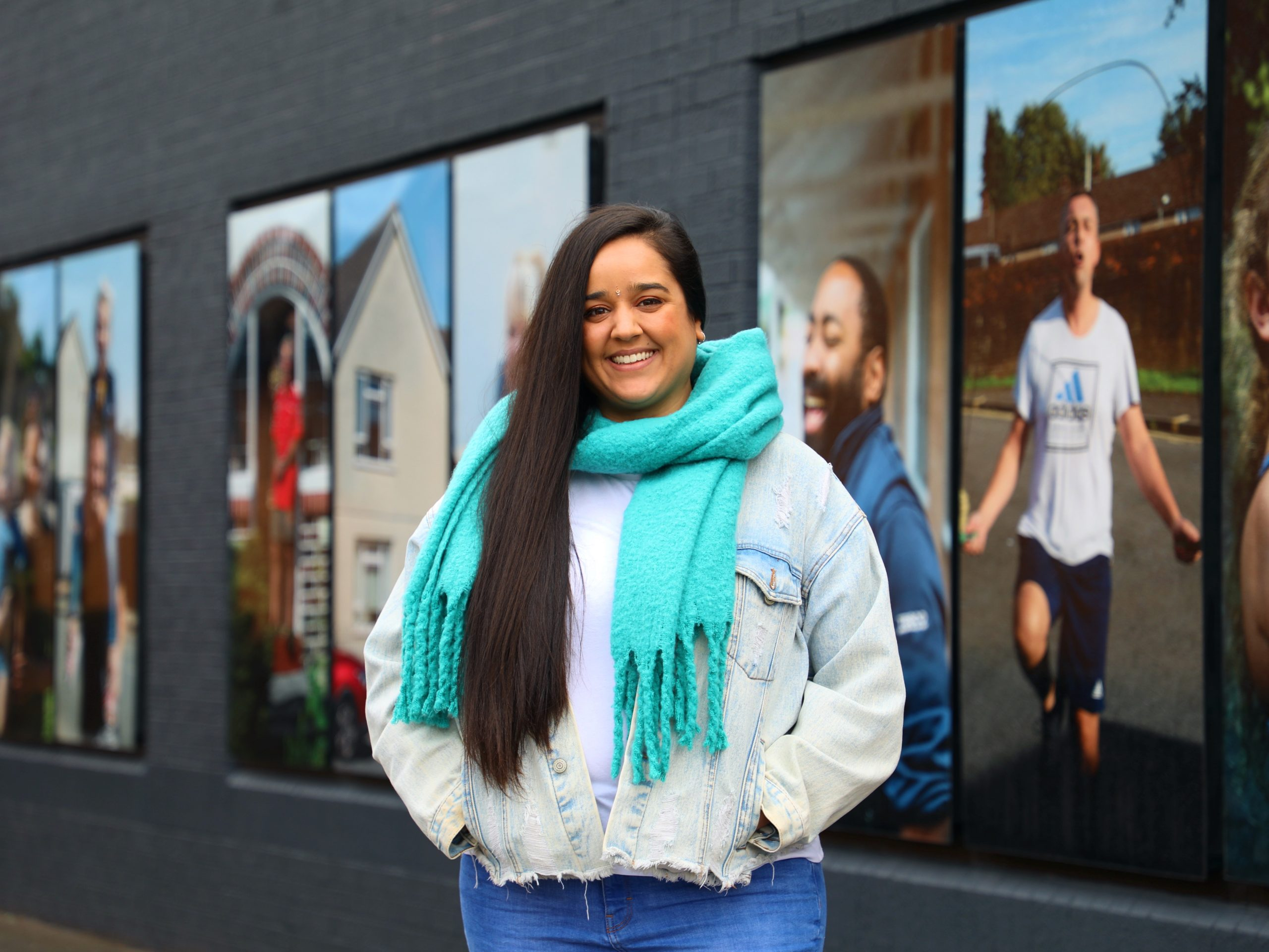 Sita stands in front of an outdoor exhibition of photographs.