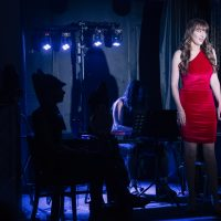 Lady in red dress singing on dimly lit stage