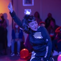 Women wearing a tracksuit dancing with balloons in the background