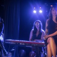Three women on stage - two singing and one playing piano