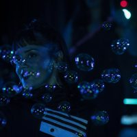 Girl in tracksuit with bubbles blown at her