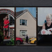 Installation shot of Us Here Now - 3 larger than life photographs showing a man in his doorway, a woman between two cars and a female boxer smiling