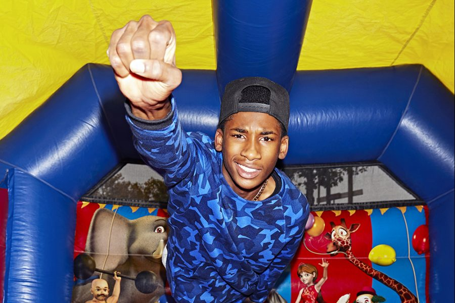 A young man flies like superman in a bouncy castle