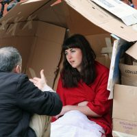 A woman sits in a house made from cardboard. She is talking to a man.