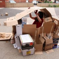 A woman sits in a cardboard house