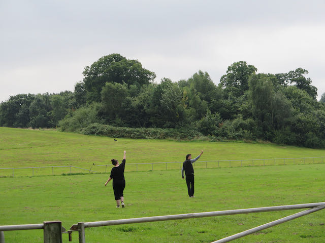 Two people walk across a field with their arms raised