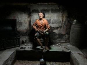 A model of a pirate with a ball and chain, sits on a chair in a cellar.
